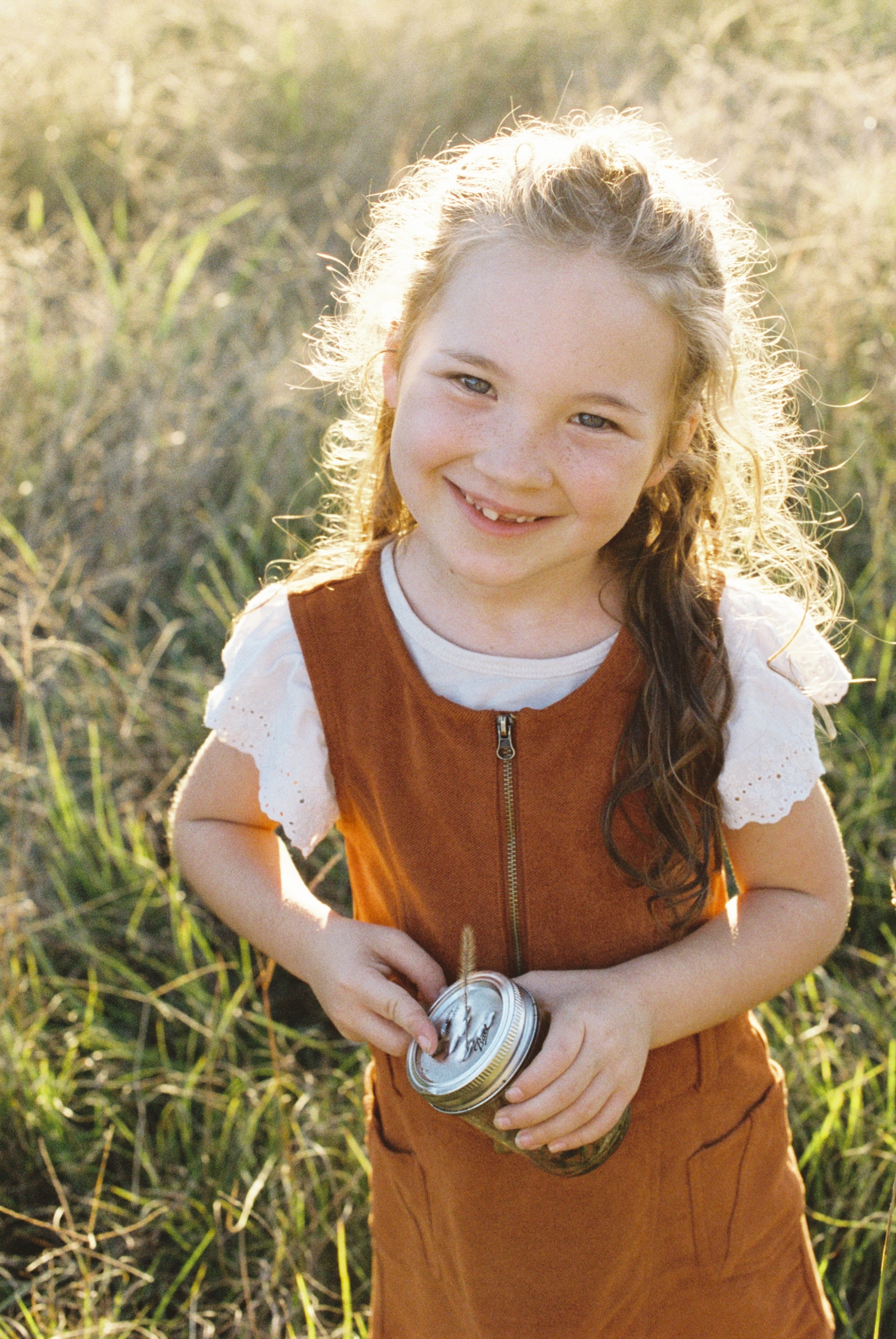 girl-holding-jar-in-field